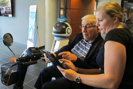 Elderly man and aide view a tablet device.